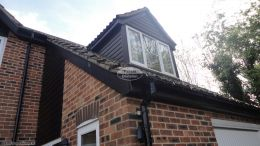 Black ash shiplap cladding around the dorma window with black ash fascia to upper and lower elevation